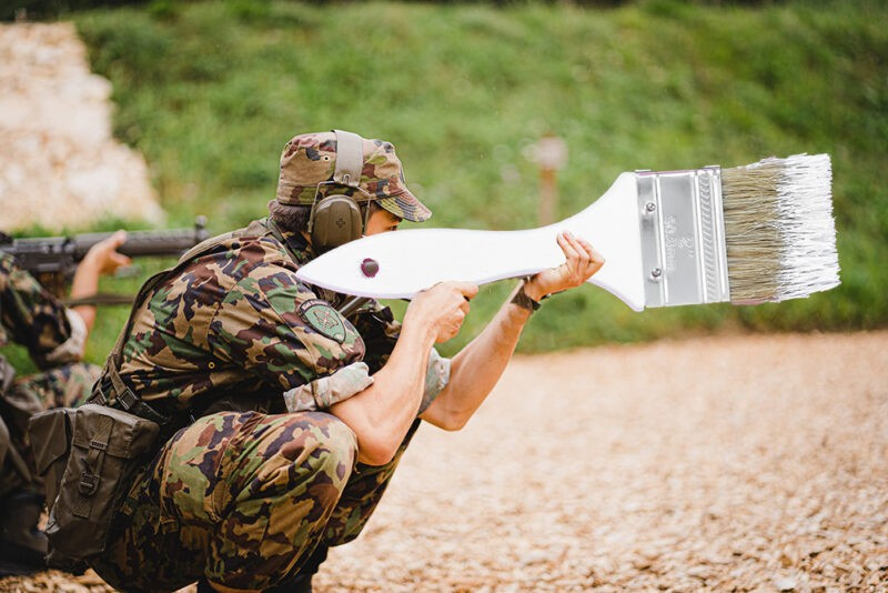 A man in military uniform holding a giant paint brush like you would hold a rifle. He is crouched, wearing ear-protectors, goggles and camouflaged clothes. The brush is white with white paint on the brown bristles. He's the soldier painting a steel shed
