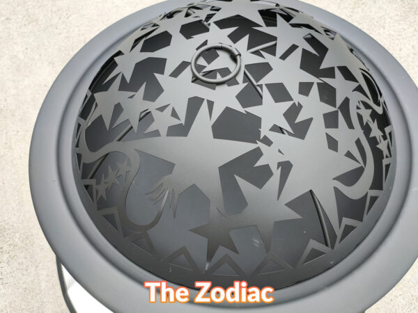 A top view of the motif on the lid of the zodiac fire pit. There are various different sized stars, a dragon's tail and some small circle on it. It's a satisfyingly nice matte black