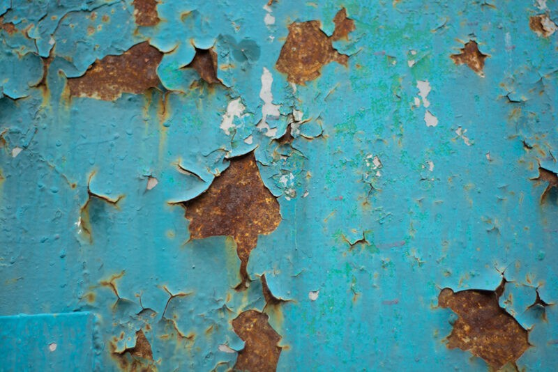 a close up of a piece of metal which was painted a teal-blue colour, but which now has large pockets of brown rust cutting through the paint
