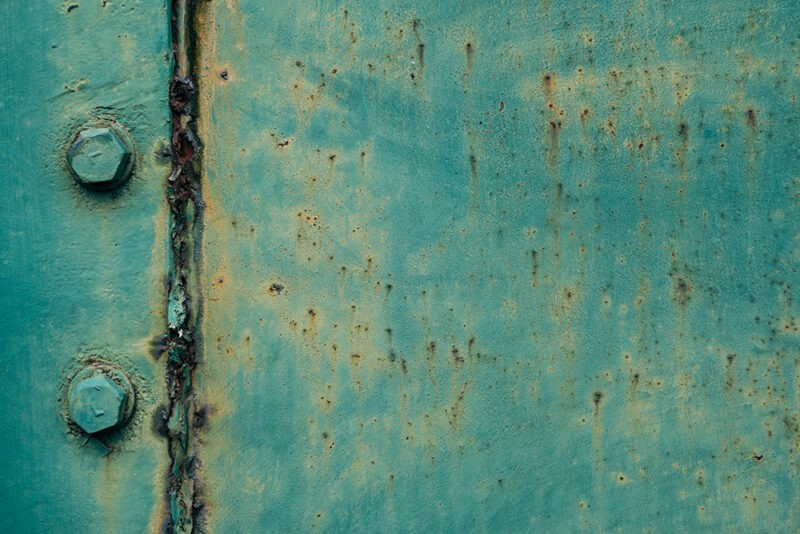 A green and blue faded piece of metal seen up close. There are two rivets to the side which have a slight brown rust around them. There is a hinge to the left which is a darker colour also