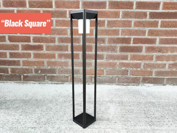 The Black Square LED garden light from sheds direct ireland. It is a tall, ractangular shape. There is a tubular light protruding downwards from the inside of the top part and it is an opaque white colour. The unit is made of whin black bars.