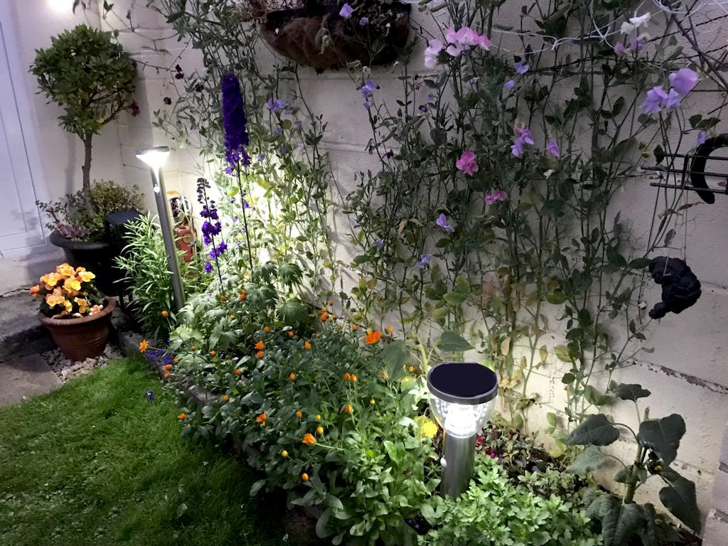 Two LED Garden Lights in a flower bed. The one closer to the camera is small, the other is very tall. They are both operational and they are illuminating the orange and purple flowers below them. There are hanging plants above the lights also, but these are in a half-light.