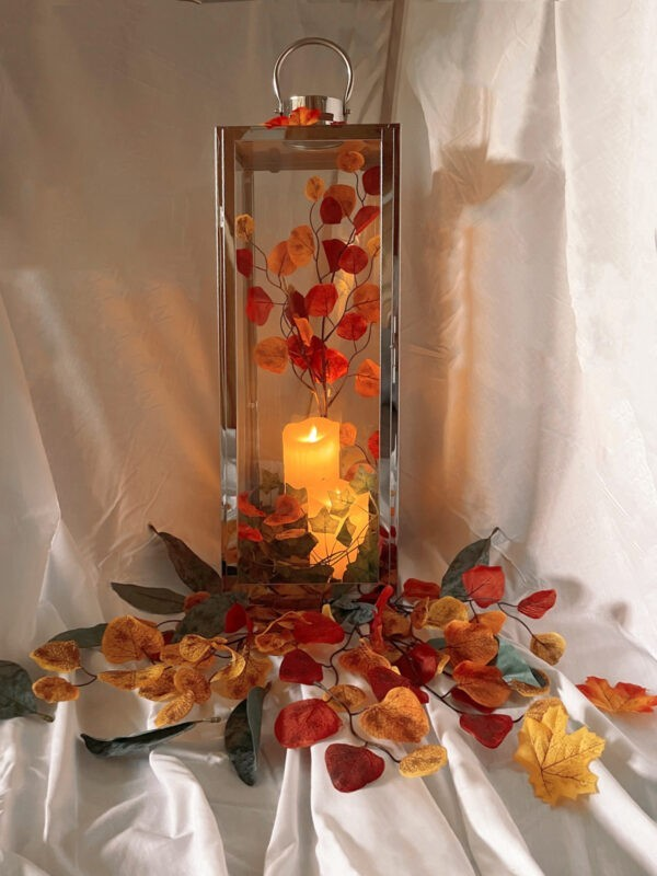 An Autumnal scene in a candle holder. The candle holder is infront of a white cloth background, there are various types of leaves at the base in various autumn colours and there is an orange candle inside the candle holder.