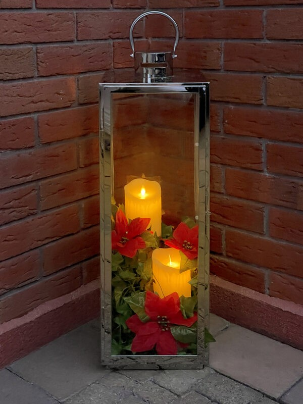 A Candle Holder with red flowers and yellow candles inside. The candle holder is in a corner, with two red-brick walls either side of it. The candles are glowing a warm orange in colour.