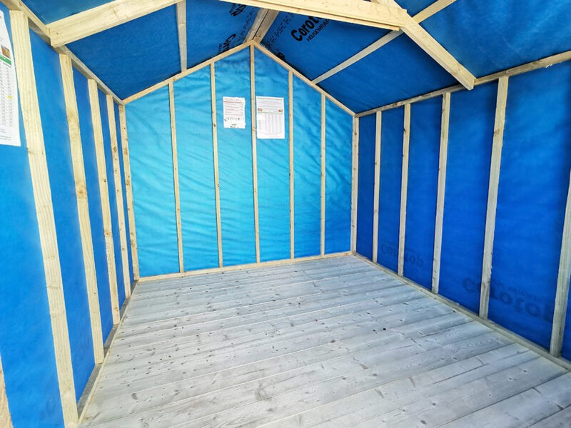 The inside of an 8ft x 8ft barrel board wooden shed which is showing the internal blue membrane up against the side walls