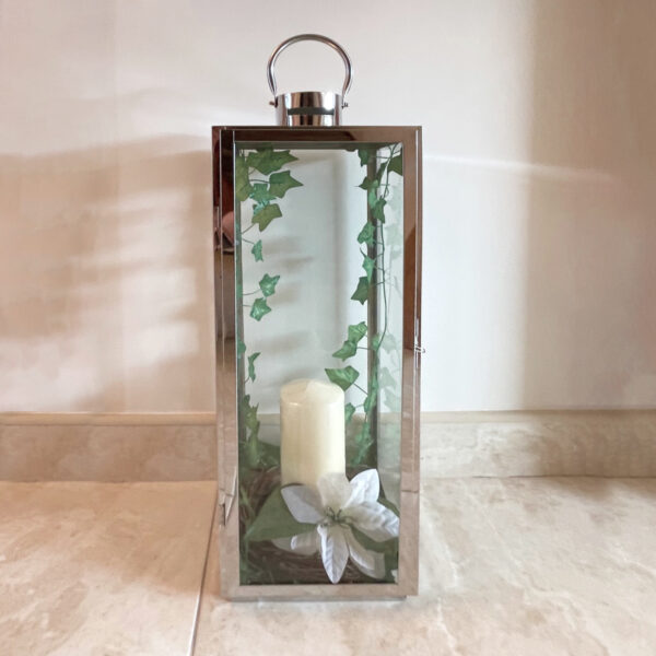 A silver, lantern-style candle holder with green leaves trailing down the inside on both edges, with a cream-coloured candle in the middle. There is a large white lily opened at the base of the candle. The candle stands on a white marble floor against a white wall.