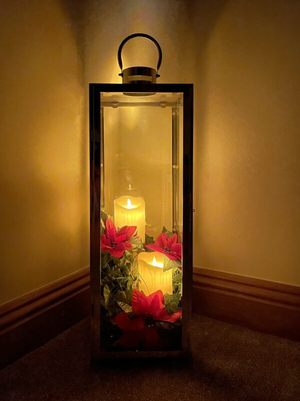 A candle holder lit exclusively by the candles inside, in an otherwise dark room. The candles are a yellow colour and there are red flowers along the bottom of it.