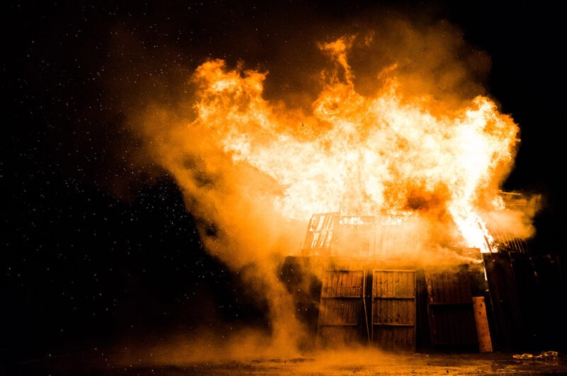 A wooden shed that is engulfed in bright orange flames. There is no other light in the scene, so it is black at the background and the shed is glowing orange