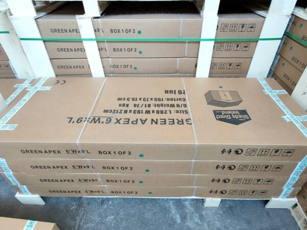 A stack of flat-packed boxes of sheds ontop of each other. There are 4 large and wide boxes on top of each other. They are brown and the text on top is upside-down and it reads 'GREEN APEX 6 FOOT X 9 FOOT'